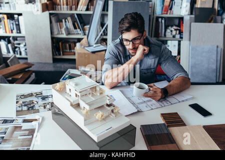 Young male architect taking break from work. Creative designer in office looking at model with cup of coffee. - Stock Photo