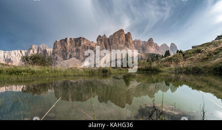 Sella Group with Piscadu reflected in a pond, Gardena Pass, Passo Gardena, nature park Park Puez Iceman, Dolomites - Stock Photo