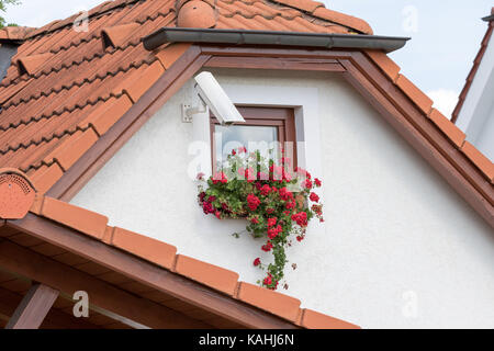 Cesky Krumlov, Czech Republic - August 17, 2017:Camera installed on a wall of a home with a small window and flowers - Stock Photo