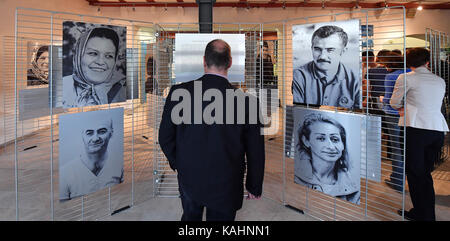 Visitors look at pictures at the exhibition 'Von Mensch zu Mensch. Ich habe einen Namen' (lit. From human to human. - Stock Photo