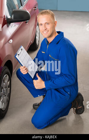 Portrait Of A Happy Mechanic Holding Clipboard - Stock Photo