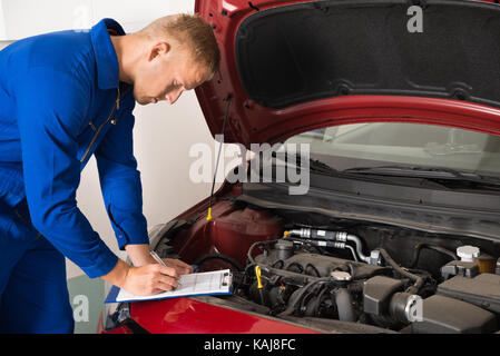 Mechanic Standing Near Car Writing On Clipboard In Garage - Stock Photo