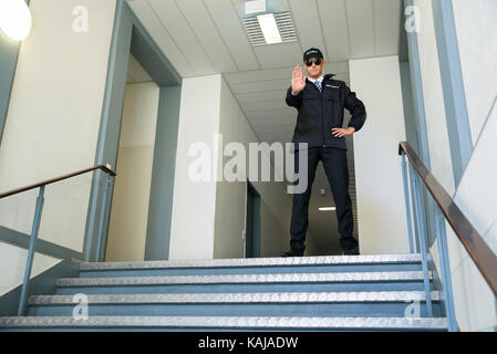 Confident Male Security Guard Standing In Front Of Entrance Making Stop Gesture - Stock Photo