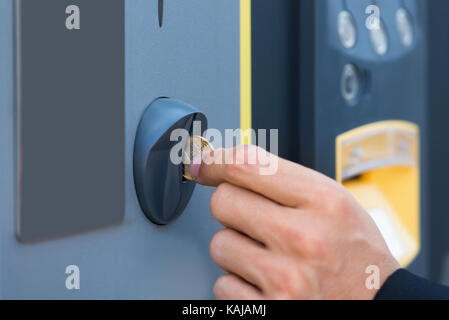 Close-up Of Person's Hand Inserting Coin At Parking Meter - Stock Photo