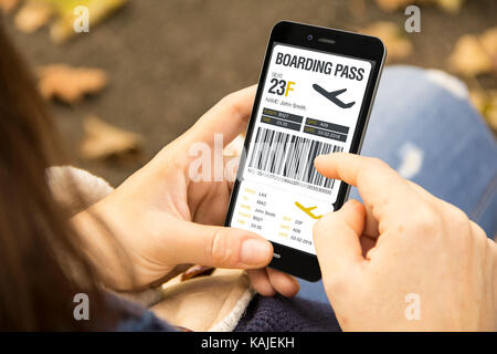 mobile app concept: woman holding a 3d generated smartphone checking boarding pass on the screen. Graphics on screen - Stock Photo