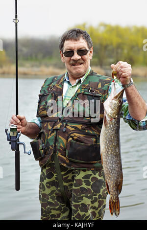Portrait of a mature fisherman with his catch beside the river - Stock Photo
