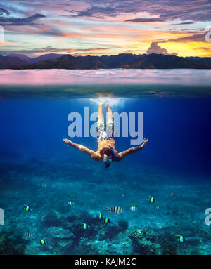 Underwater shoot of a young man snorkeling in a tropical sea and colorful sunset splitted by waterline. Design template - Stock Photo