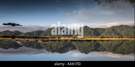 Upside down! Beautiful mirror like reflection of the hills in the Aorere River Inlet by Collingwood, Tasman/ South - Stock Photo