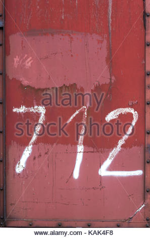Red, weathered metal wall of a cargo container. White numbers painted on it. Seven, one, two, 7, 1, 2. Full-surface - Stock Photo