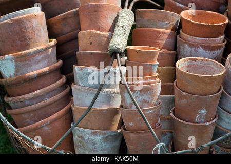 Wire basket of clean terracotta flower pots getting ready for storage over the winter period. UK - Stock Photo