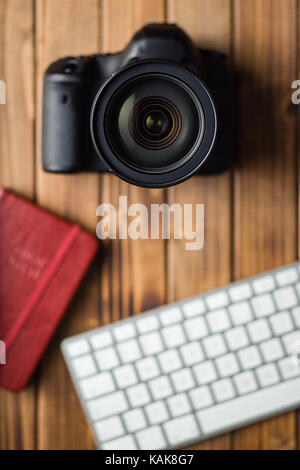 Professional digital camera and computer keyboard on wooden table. - Stock Photo