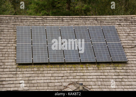 solar panels on a traditional shingled roof - Stock Photo