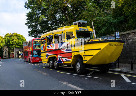 An amphibious vehicle owned by Windsor Duck Tours is parked on the side of the road with a double decker tour bus - Stock Photo
