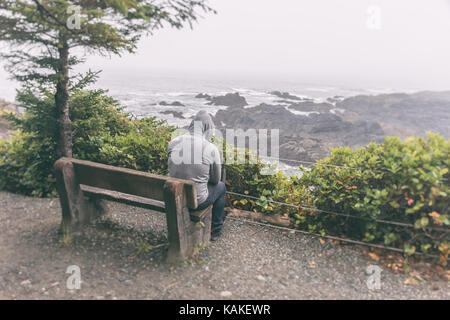 Sad and lonely man sitting on bench overlooking sea on Vancouver Island - Stock Photo