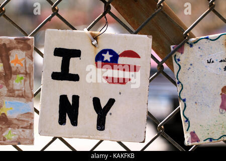 A hand painted ceramic tile with i love New York City written across it and. Then left to hang on a wire fence that - Stock Photo