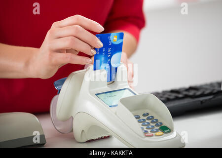 Midsection of saleswoman swiping credit card on reader at store - Stock Photo