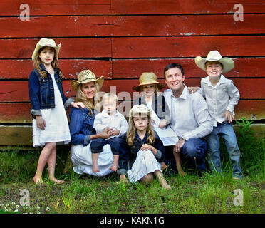 Family of seven pose besides red, wooden barn.  Females are wearing denim jackets and cowboy hats.  Males are wearing - Stock Photo