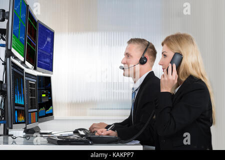Young business people analyzing data displayed on computer screens in office - Stock Photo