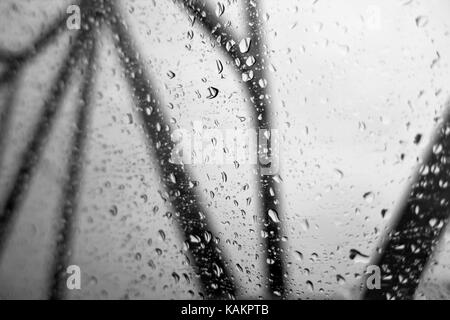 Looking out of windows covered with water droplets at black bridge struts on a gray sky. Concept. - Stock Photo