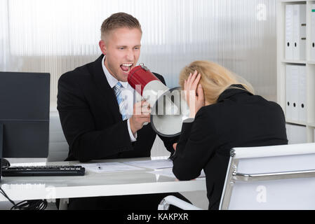Boss shouting at businesswoman through loudspeaker at desk in office - Stock Photo