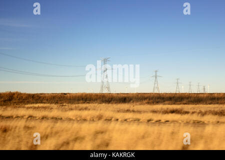 A line of high voltage power lines in a brown meadow. - Stock Photo