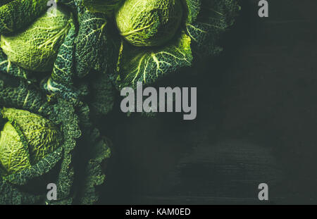 Raw fresh uncooked green cabbage over dark background, copy space - Stock Photo