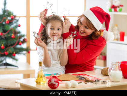 Mother and child daughter making Christmas cookies and having fun. - Stock Photo
