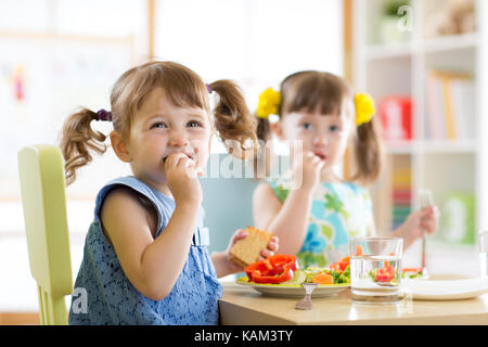 Cute little children eating food at daycare - Stock Photo