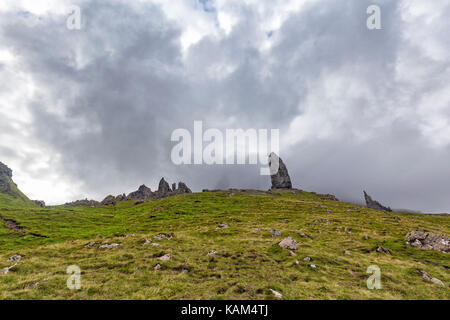 Grey summer fog passes over the Old Man of Storr on the Isle of Skye in Scotland. - Stock Photo