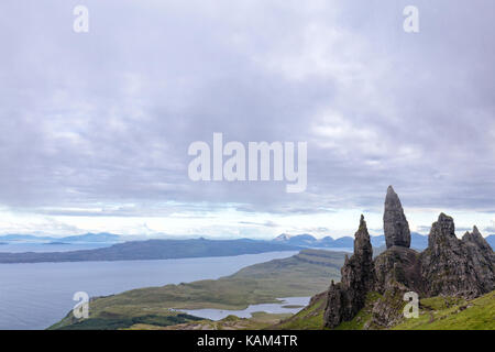 Grey summer mist passes over the Old Man of Storr on the Isle of Skye in Scotland. - Stock Photo