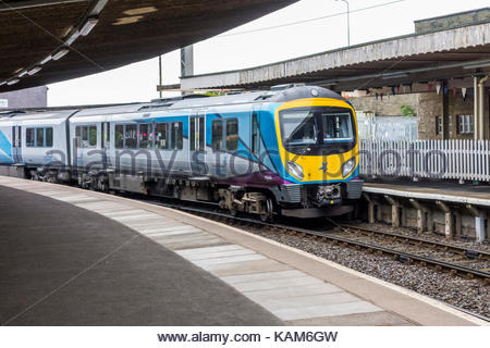 A train for Manchester Airport enters the platform at Carnforth Railway Station - Stock Photo
