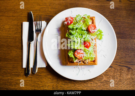 The above composition of the food. The belgian waffles with vegetables such as tomatoes, salat and cheese. - Stock Photo