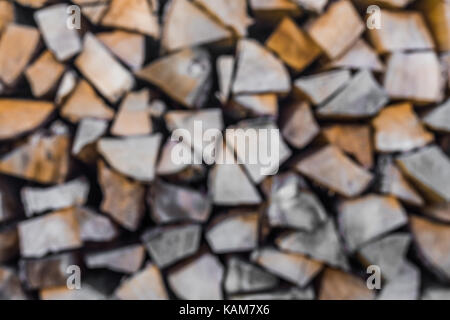 Abstract blurred stack of dry firewood as background. - Stock Photo