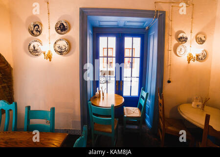 The horizontal photo of the bright chairs with table standing next to the blue door in the romantic vintage cafe. - Stock Photo