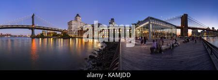 Panoramic night view of the newly renovated Brooklyn waterfront between the Manhattan Bridge and Brooklyn Bridge. - Stock Photo