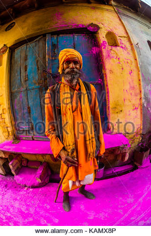 A saddhu (Holy man) walks down the street after a procession has passed throwing colored powders, Chhadi Mar Holi - Stock Photo