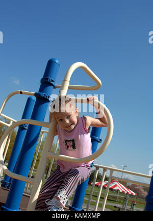 Little girl climbs through a metal hoop on playground equipment.  She is smiling and happy.  Equipment is blue and - Stock Photo