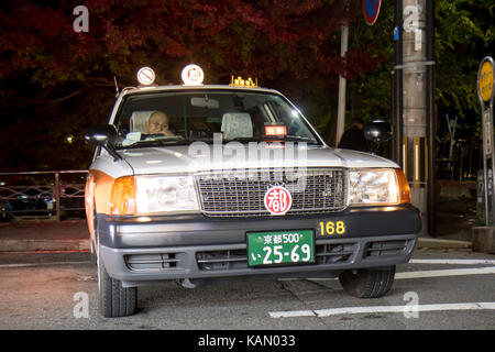 Taxi waits for customers on the streets of evening Kyoto - Stock Photo