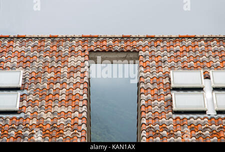 The gap between the houses is covered with a small roof. Two houses are connected by a roof. - Stock Photo