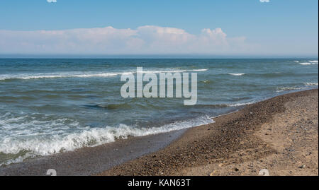 Clear Ocean Water on Rocky Beach with mostly clear skies - Stock Photo