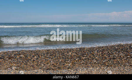 Low Angle Picture of Rocky Beach with Waves Breaking in the Background - Stock Photo