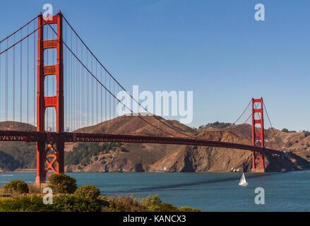 Golden Gate Bridge, San Francisco, California, USA. Single white sailboat about to pass under the bridge. Space - Stock Photo