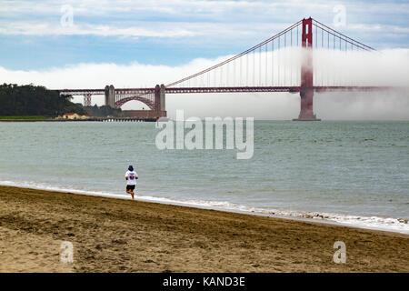 Person jogging on beach in front of Golden Gate Bridge, San Francisco, California, USA. Bridge is partially in fog, - Stock Photo