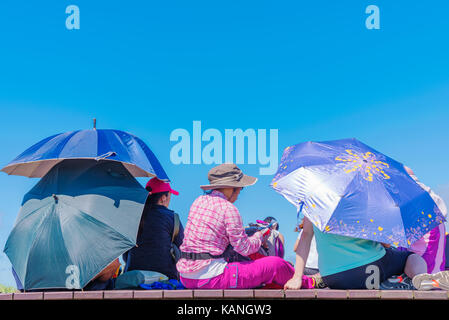 TAIPEI, TAIWAN - JULY 16: This is a goup of people resting under umbrellas from the sun on some benches at the highest - Stock Photo