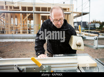 Carpenter Using Table Saw To Cut Plank At Site - Stock Photo
