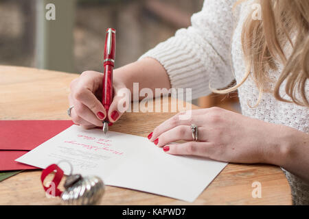 young woman writing christmas cards with red nails, a red pen, and holiday decorations on a wooden table - Stock Photo