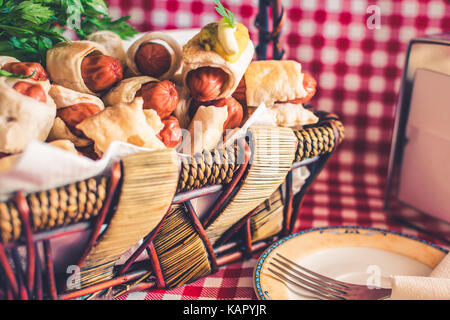 Wicker basket with mini hot dogs homemade (Sausage in the dough) and a saucer with a fork on a plaid background - Stock Photo