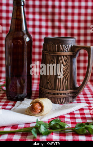 Homemade Mini hot dog (sausage in pastry) on napkin with a bottle of dark beer and earthenware mug on a plaid background - Stock Photo