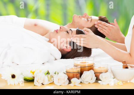 Side view of relaxed young couple receiving head massage at beauty spa - Stock Photo