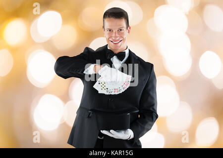 Portrait of confident young magician showing trick with playing cards against illuminated background - Stock Photo